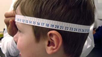 Child with measuring tape around head